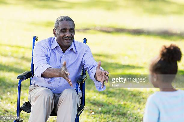 Senior man in wheelchair reaching out for grandchild