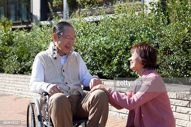 Senior man in wheelchair smiling face to face with senior woman
