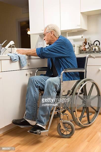 Senior man in wheelchair washing dishes