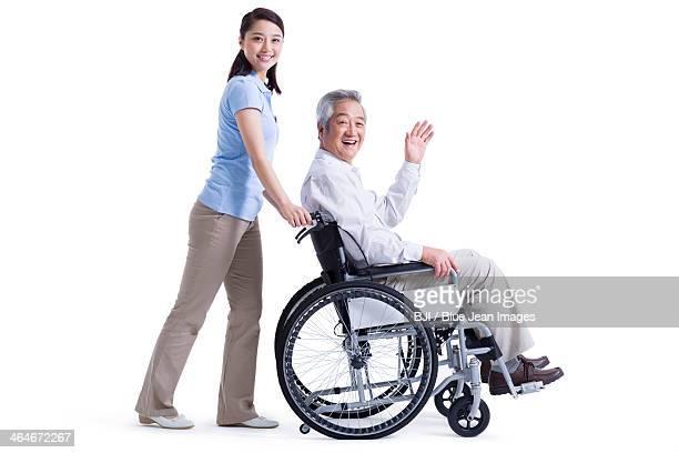 Senior man in wheelchair waving