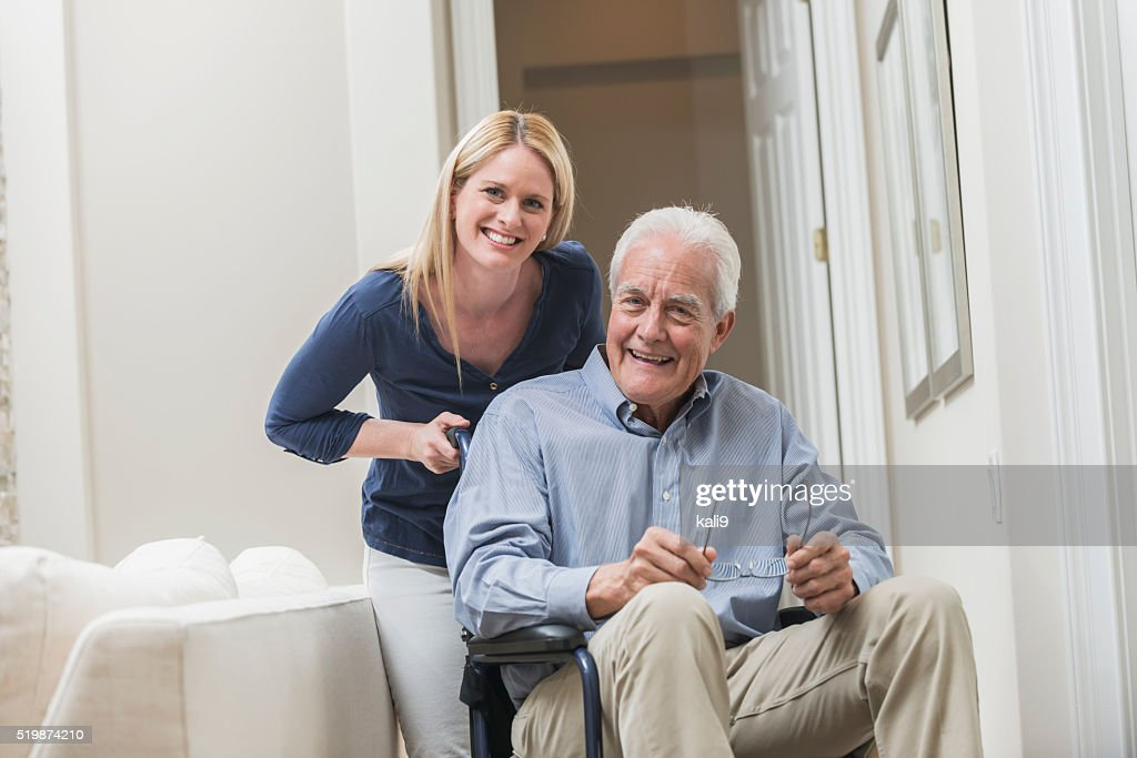 Senior man in wheelchair with caregiver at home : Stock Photo