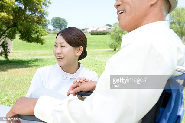 Senior man in wheelchair with female nurse, smiling