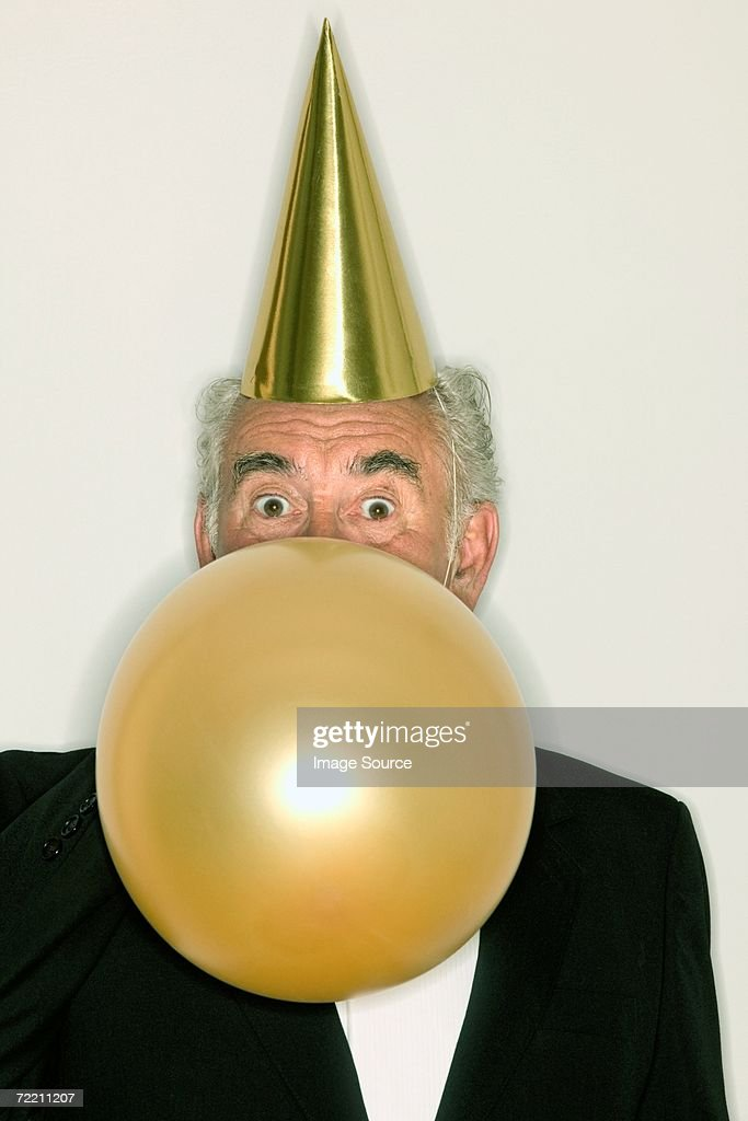 Senior man inflating a balloon