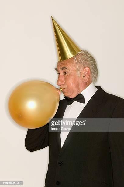 Senior man inflating a balloon