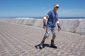 Senior man inline skating along seafront