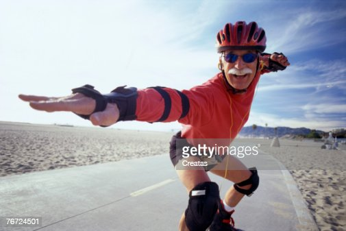 Senior man in-line skating in a surfing pose : Stock Photo