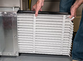 Senior caucasian man changing a folded air filter in the HVAC furnace system in basement of home
