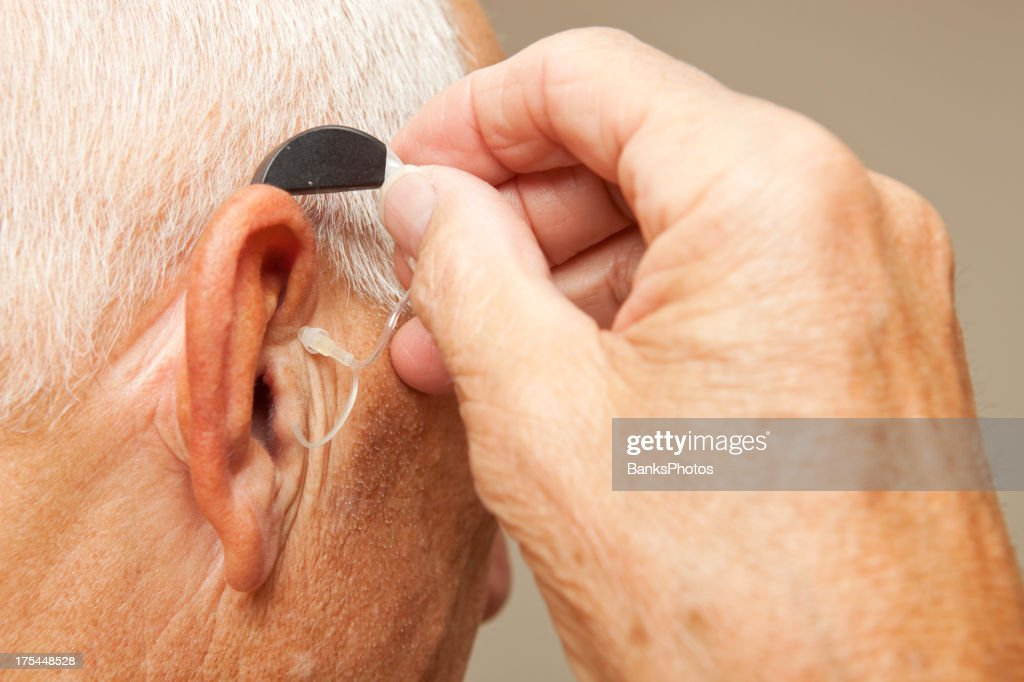 Senior Man Installing Hearing Aid : Stock Photo