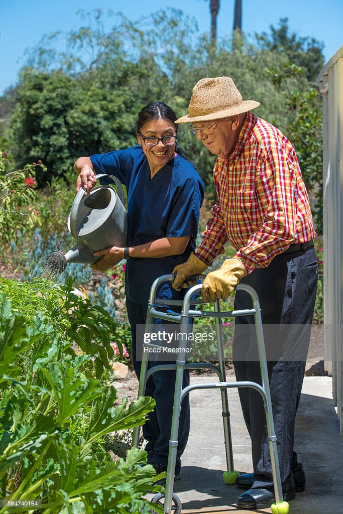 A senior man is helped by a hispanic home care giver as he waters plants in a garden.
