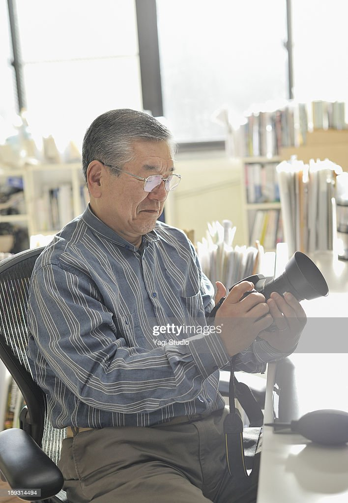 Senior man is holding a digital camera : Stock Photo