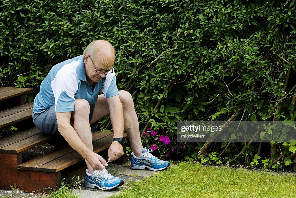 Senior man is tying a sports shoe before running