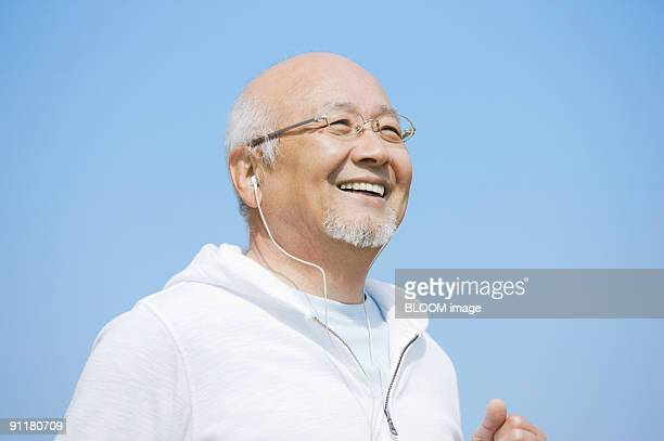 Senior man jogging, listening to music with earphones, against sky