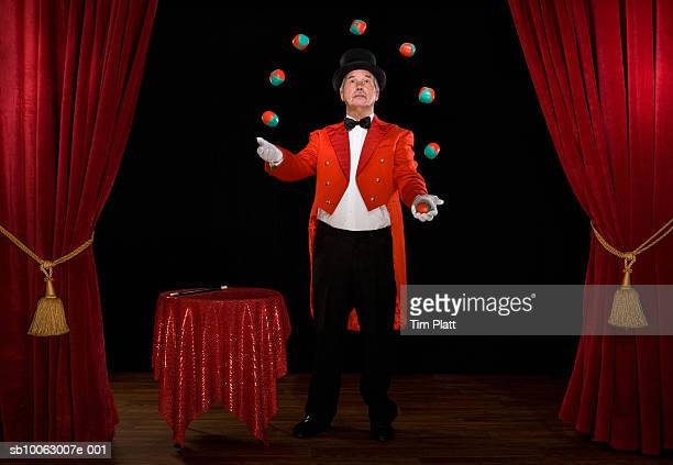 Senior man juggling balls on stage