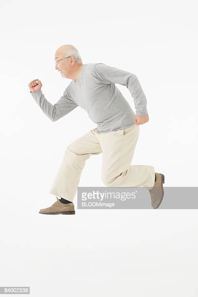 Senior man jumping, clenching fist, side view, studio shot