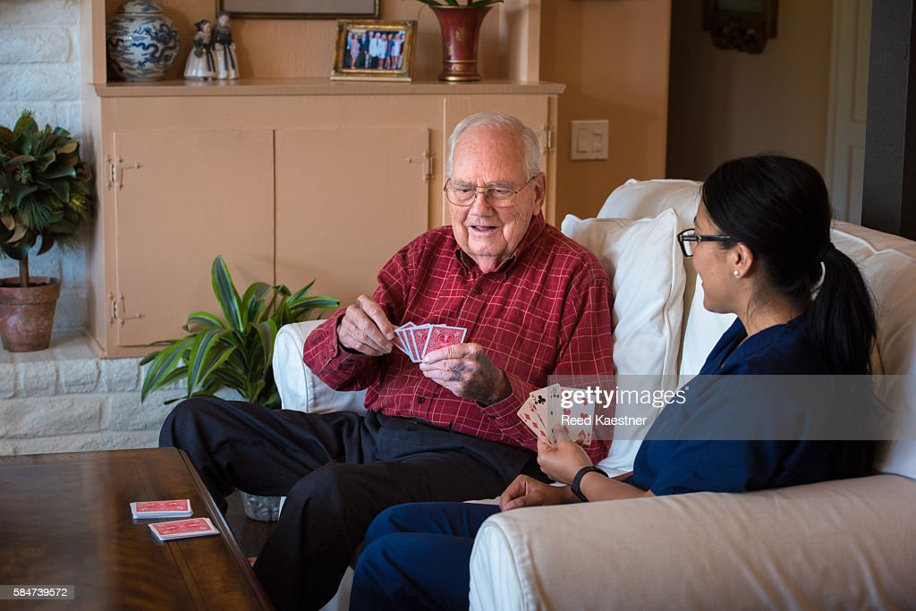 A senior man keeps his mind sharp by playing cards with a hispanic home health care nurse.