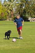 Senior man kicking soccer ball with dog in park