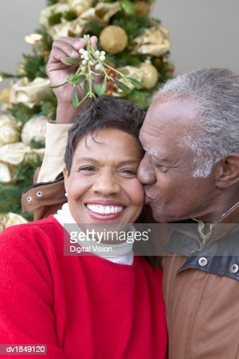 Senior Man Kissing a Senior Woman Under the Mistletoe : Stock-Foto