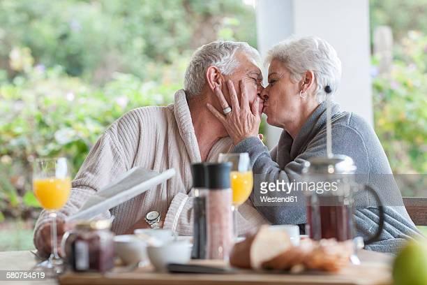 Senior man kissing her husband at breakfast table