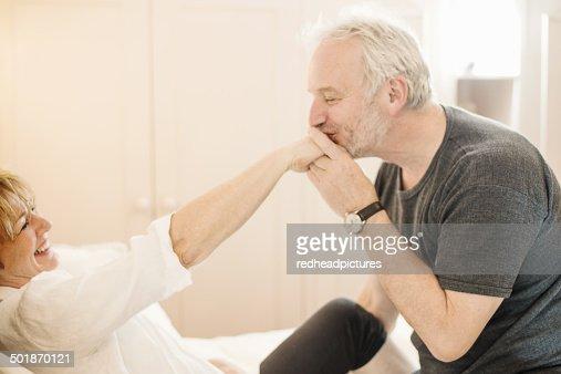 Senior man kissing mature woman's hand