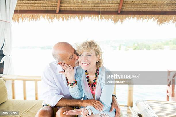 Senior Man Kissing Smiling Wife on Cheeks, Summer, Beach, Europe
