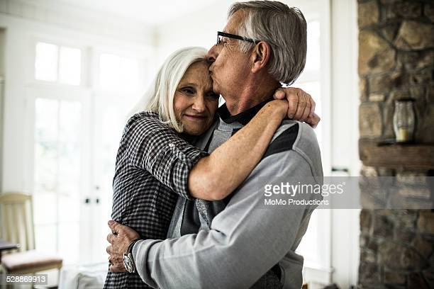 Senior man kissing wife on forehead