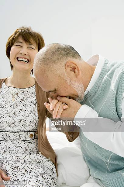 Senior man kissing wife's hand, woman laughing, close-up