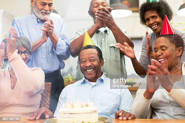Senior man laughing at birthday party, Cape Town, South Africa