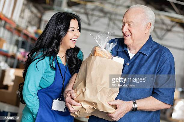 Senior man laughing with food donation volunteer