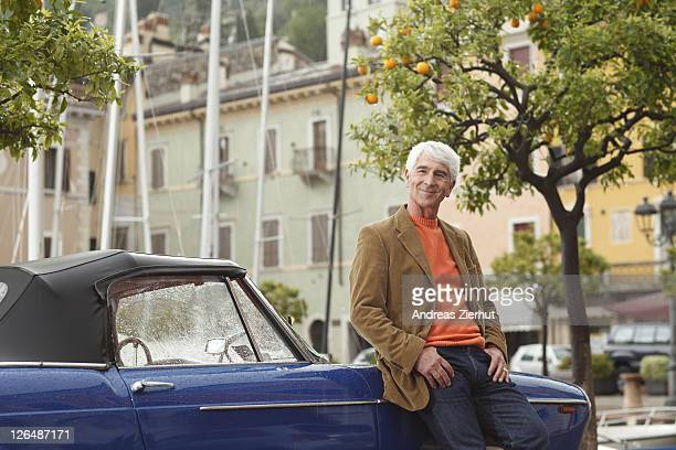 Senior man leaning against vintage car at harbor, Italy