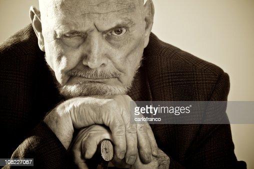 Alter Mann schiefen Kopf auf seine Cane, Sepia