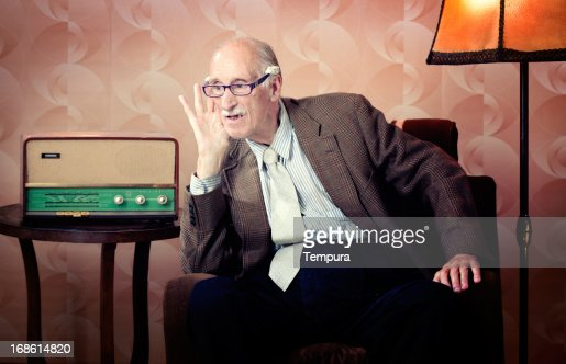Senior man leaning in to listen to retro radio