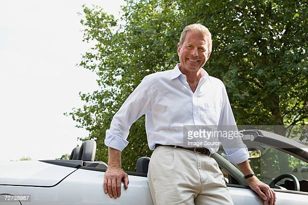 Senior man leaning on convertible