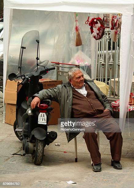 Uomo anziano, appoggiato sul suo moto scooter Napoli vita reale