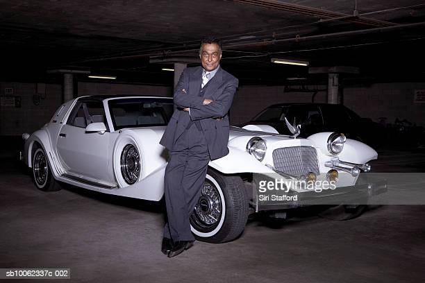 Senior man leaning on luxury car