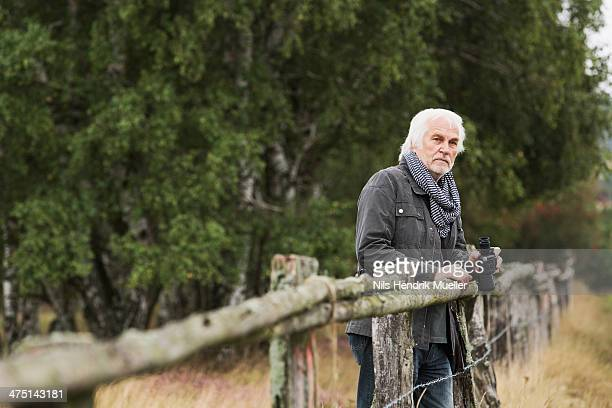 Senior man leaning on wooden fence with binoculars