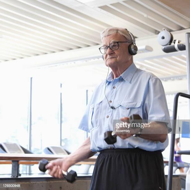 Senior man lifting weights in health club