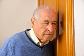Cropped shot of senior man listening through door of house as concept of gossip man