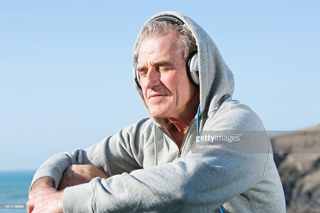 Senior man listening through headphones : Stock Photo