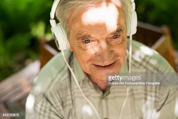 Senior man listening to music on headphones in garden
