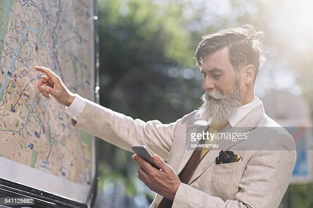 Supérieur homme regardant une carte de la ville de Paris