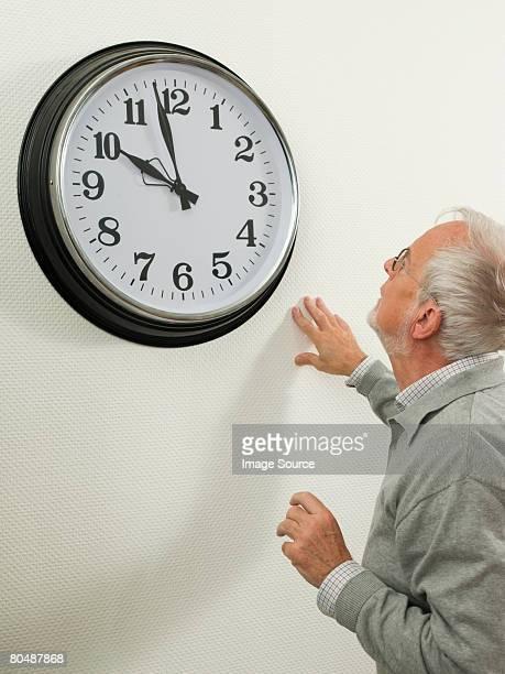 Senior man looking at a large clock
