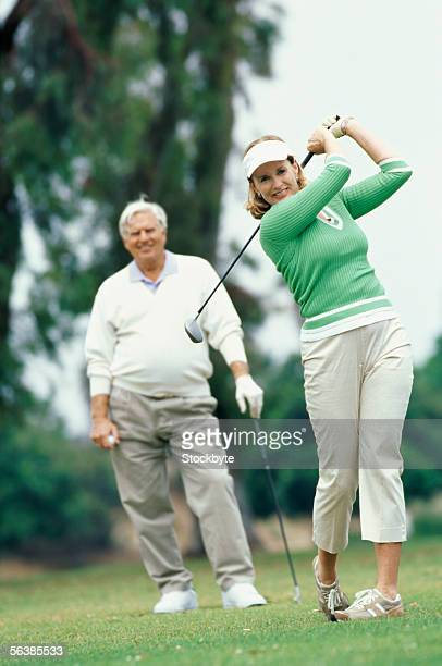 Two mature women playing golf, brunette sitting in golf