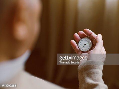 Senior man looking at a vintage watch