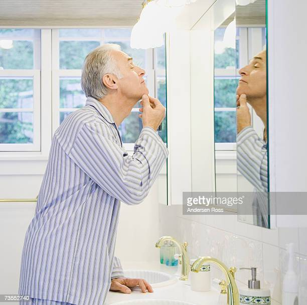 Senior man looking at face in bathroom mirror