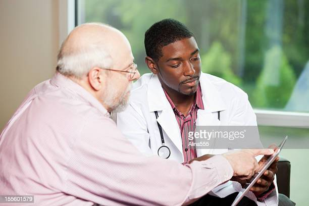 Senior man looking at information on digital tablet with doctor