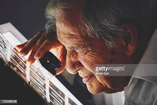 Senior man looking at sheet of film slides with magnifier
