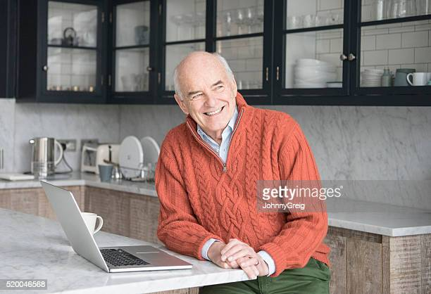 Senior man looking away in kitchen with laptop