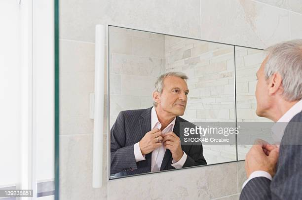 Senior man looking in bathroom mirror buttoning his tie