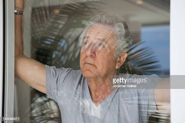 A senior man looking out a window