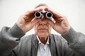 Senior man looking through binoculars, close-up